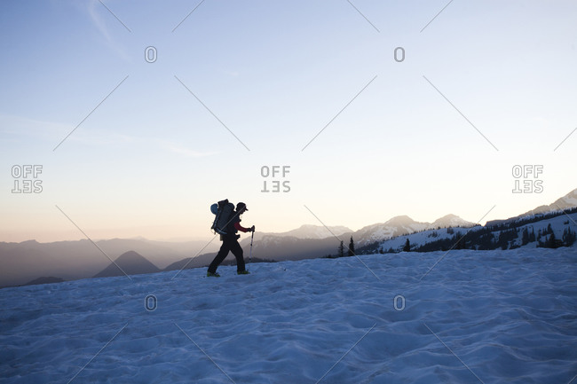 One skier skins up a snowy trail as the sun sets over the distant  mountains