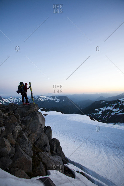 A climber stands silhouetted against an evening sky on a rocky outcrop with skis in hand