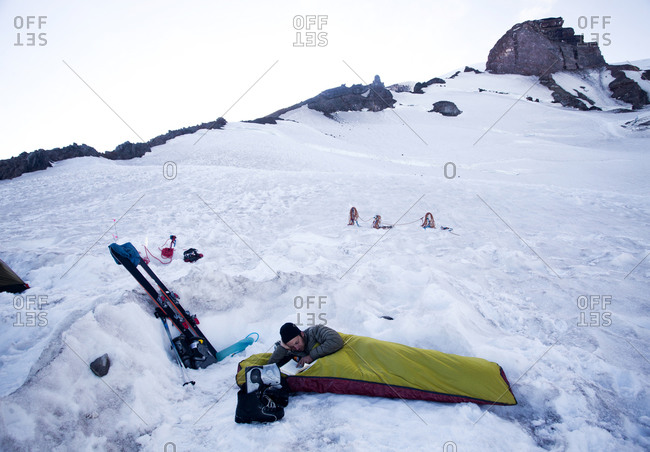 A young climber lies in his bivy sack and reads a book while the sun sets at base camp on Mount Rainier