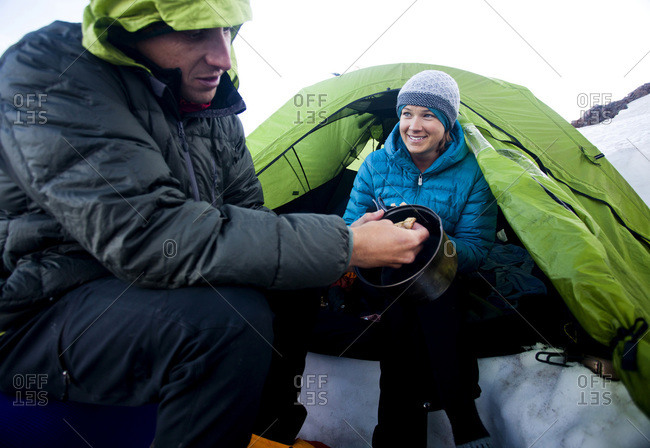 A couple enjoy camping at base camp and eating food before climbing to the summit of the volcano