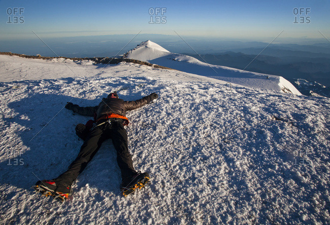 An exhausted climber lies on the summit of Mount Rainier on a blue bird day