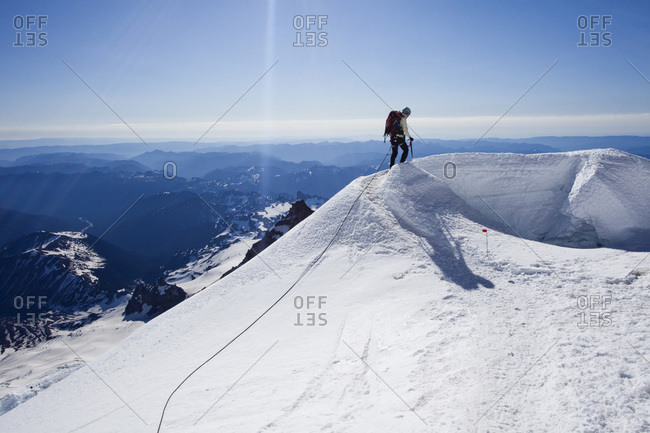 A climber descends a snow covered mountain on a sunny day while attached to a rope