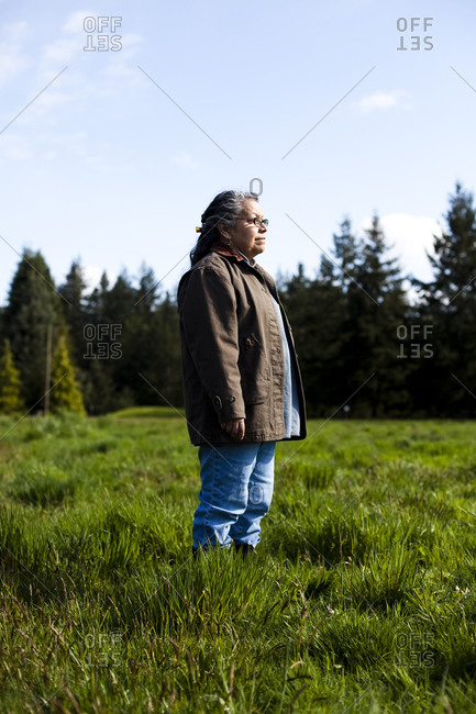 A portrait of a woman in a field on a sunny day