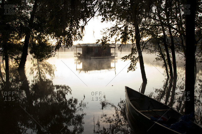 A canoe and a house boat at dusk on a river with mist