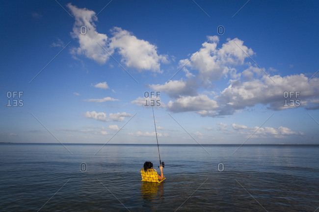 A woman sits in a lawn chair in shallow water waiting for a fish to bite on a sunny day