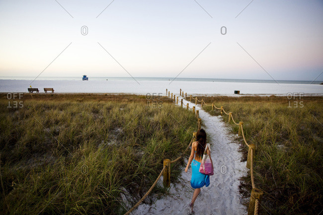 A young girl walks down a path to the beach at sunrise