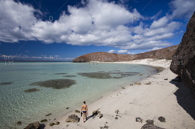 A young girl wearing a bikini walks on a lonely beach next to the clear, blue waters of the Sea of Cortes outside La Paz, Baja California Sur, Mexico