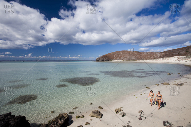 Two young girls wearing bikinis walk on a lonely beach next to the clear, blue waters of the Sea of Cortes outside La Paz, Baja California Sur, Mexico