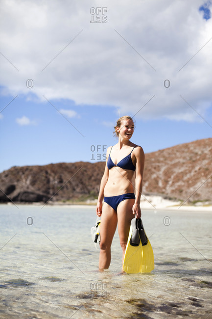 A young girl wearing a bikini and holding snorkeling gear wades in the clear waters of the Sea of Cortes outside La Paz, Baja California Sur, Mexico