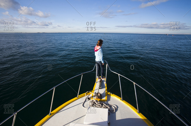A young woman rides at the front of a boat overlooking the deep blue waters of the Sea of Cortes outside La Paz, Baja California Sur, Mexico