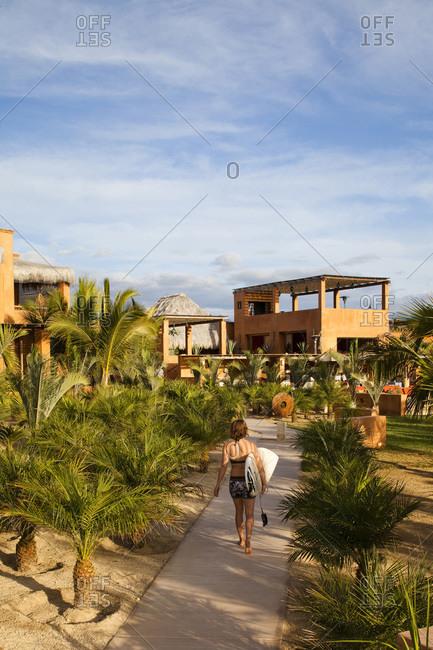 A girl walks her surfboard down the path towards a boutique hotel on the beach in Pescadero, Baja California Sur, Mexico