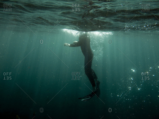A diver wearing flippers floats in the deep green water near Sea of Cortes near La Paz, Baja California Sur, Mexico