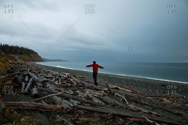 A man balances on logs on a beach after sunset near Ebey's Landing, WA