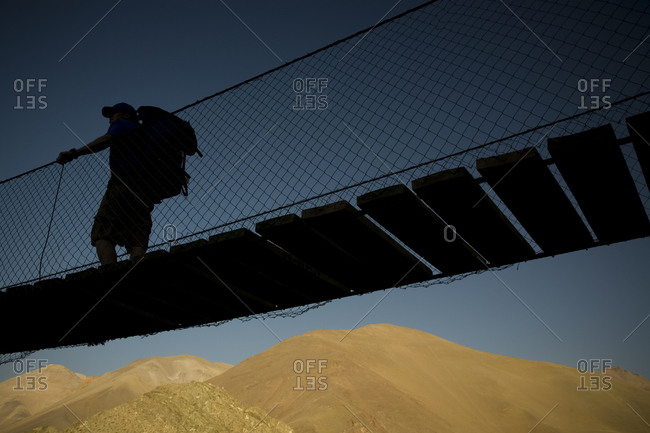 A backpacker crosses a bridge on the way into the Andes Mountains of Chile
