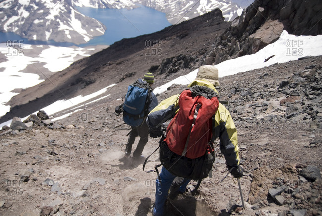 Two climbers descend the steep scree slopes after climbing Volcan Planchon