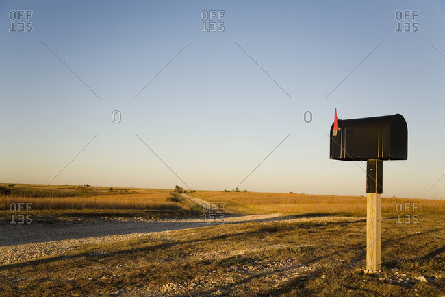 A mailbox stands alone in a Kansas corn field as the sun sets beyond the horizon