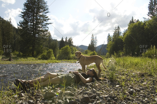 A young girl rest comfortably with her dog next to a small stream in Montana
