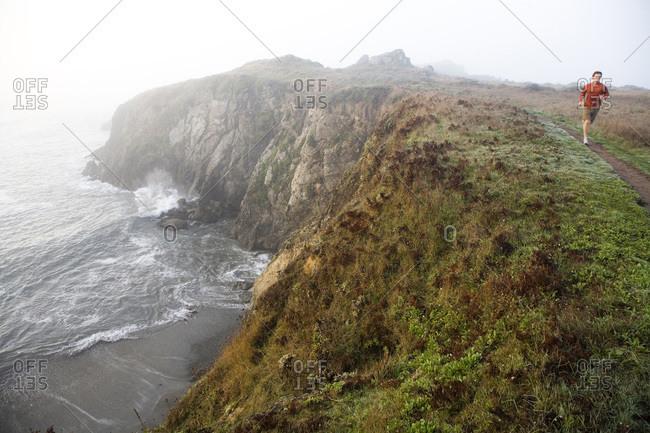 A man runs along a small trail on the coast of California