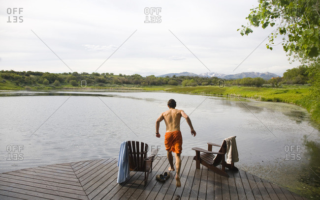 A young man runs on a dock before jumping into the cold water, Durango, Colorado