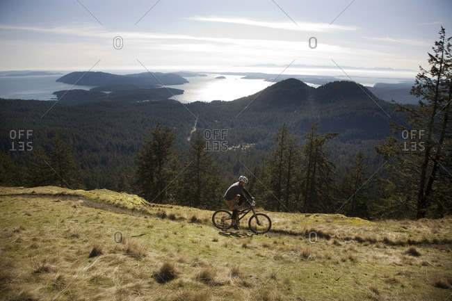 A mountain biker begins to descend a slope overlooking the San Juan Islands, Washington