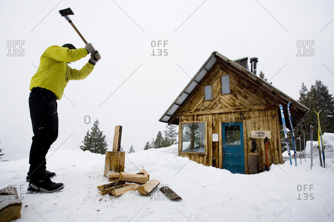 A young man chops wood in front of a small cabin in the mountains, Winthrop, Washington