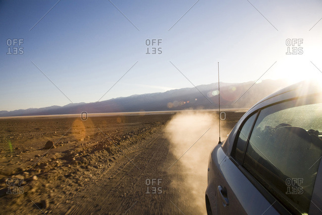 A car speeds down a sandy road leaving behind a dust trail