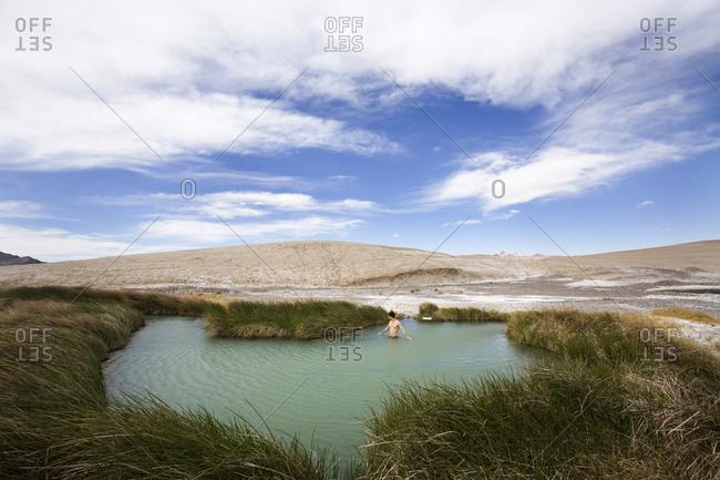 A man walks into a hot spring among an empty valley Tecopa, California, USA