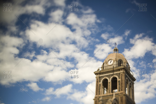 A clock tower stands out against a blue sky scattered with puffy clouds in Loreto, Baja California Sur, Mexico