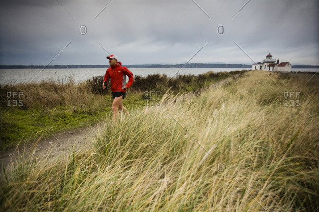A runner follows a trail along the Puget Sound at Discovery Park, Seattle, WA