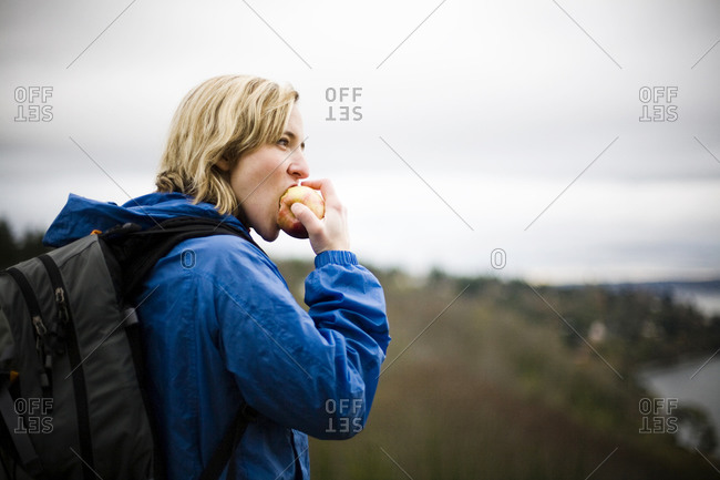A young woman snacks on an apple while walking through Discovery Park on a cloudy