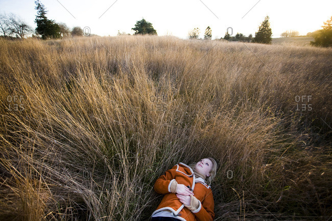 A young girl lying down in a field