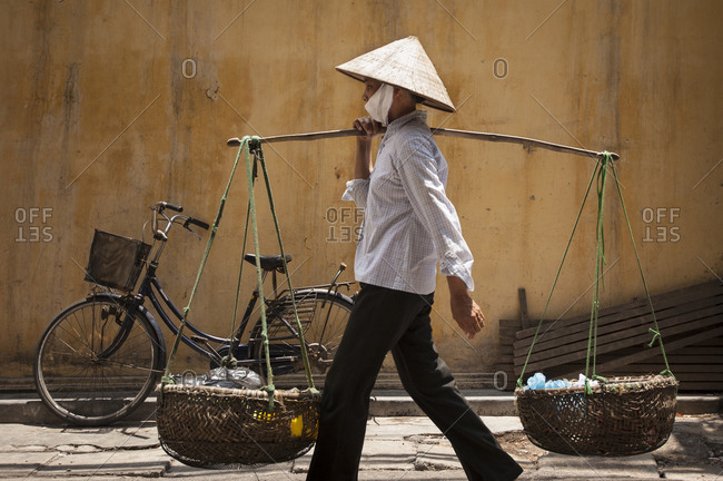 Hanoi, Vietnam - May 9, 2012: A woman carrying goods on Hanoi street