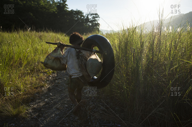 A Mangyan man walking to the Bongabon River to transport goods down river