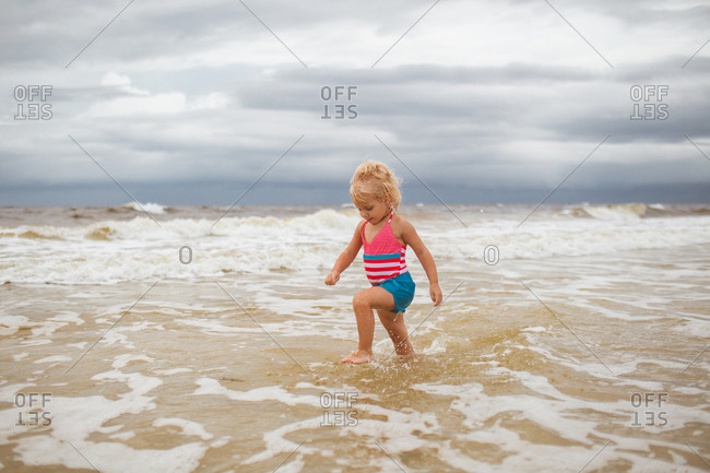 A little girl marches through the ocean tide