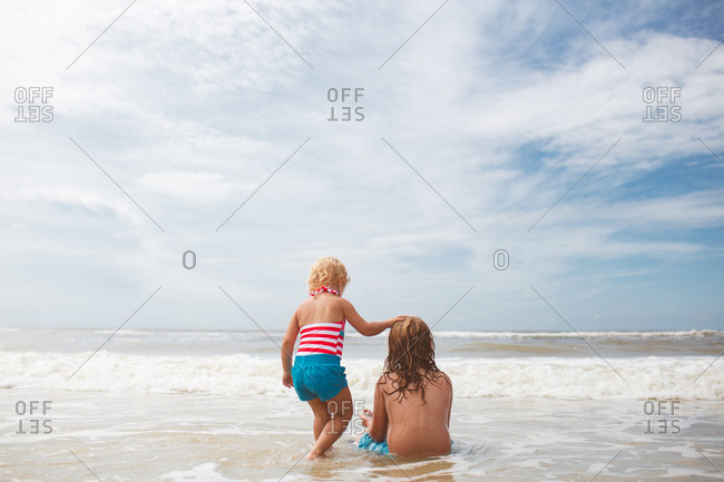 A girl and her brother play in the ocean
