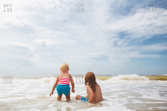 A girl and her brother watch a wave come towards them