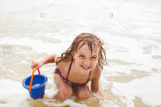 A little girl crouches in the ocean