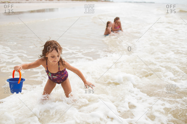 A little girl braces herself for an oncoming wave