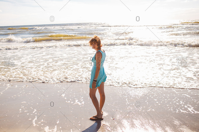 A woman stands at the edge of the ocean