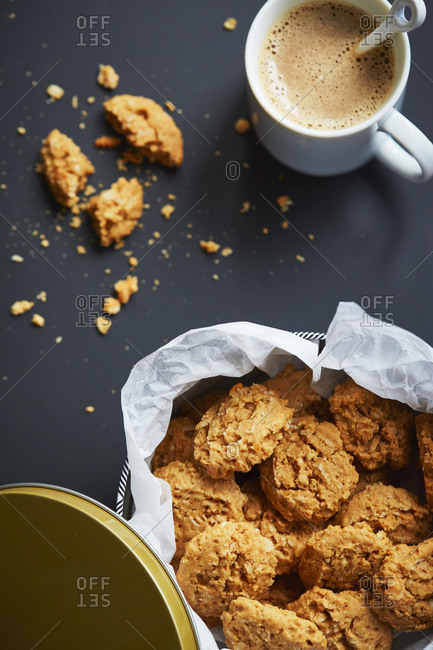 A tin of oat cookies with coffee