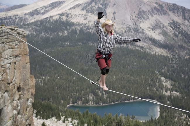 Male highliner in cowboy hat walks a 125 foot highline over a lake in a gap on top of Mammoth Crest