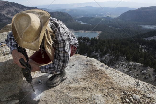 Professional highliner drilling holes in solid rock to bolt and establish a highline anchor on top of Mammoth Crest