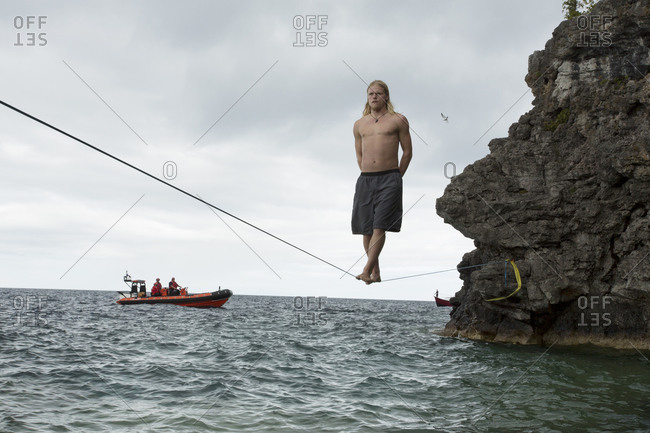 Male slackliner standing straight with arms folded behind the back on a 90 ft waterline while a patrol boat watches from a distance