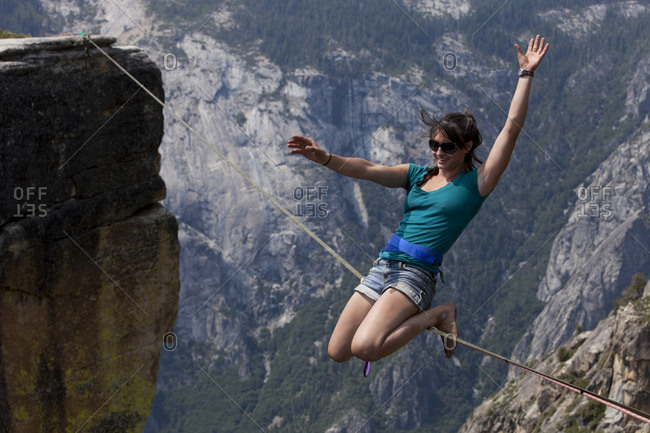 Emily Sukiennik wearing a swami style safety leash doing the double drop knee pose on a highline one thousand meters above the Yosemite Valley floor at Taft Point