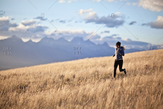 A woman trail runs near Jackson, WY with the Teton Mountains looming in the background