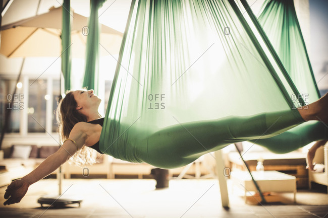 A woman holding a pose in aerial yoga.
