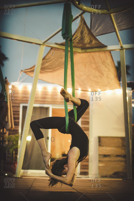 A woman performs aerial yoga.