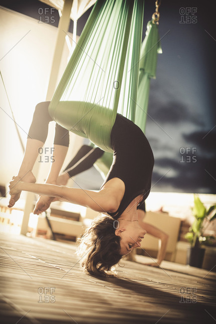 Two young ladies perform aerial yoga.