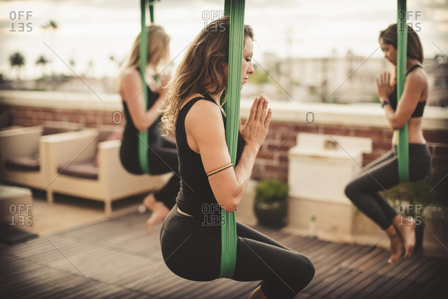Three young women perform aerial yoga.