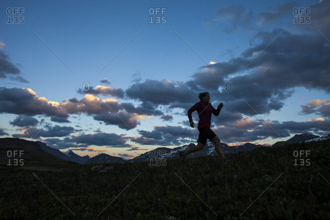 A woman trail runs Parker Ridge in Banff National Park, Alberta Canada.